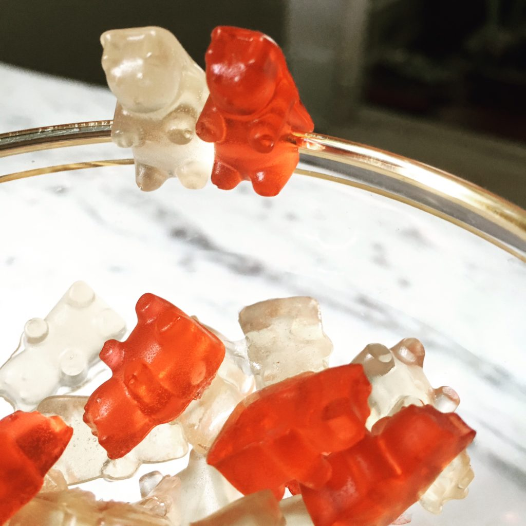 gummy bears perched on a glass